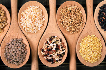 Variety of rice and grains in wooden spoons close up