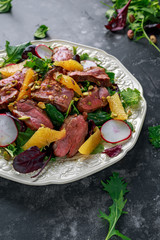 Duck breast fillets steak salad with orange halves, radishes and crushed pistachios