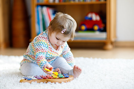 Adorable cute beautiful little baby girl playing with educational wooden music toys at home or nursery. Toddler with colorful xylophon