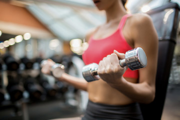 Midsection of sporty girl with dumbbells exercising in fitness club
