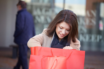 young woman sitting at the bench with shopping bag