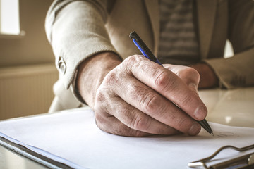 Businessman hand sign papers. Close up..