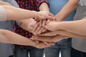 Young people putting hands together as symbol of unity, closeup
