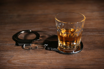 Glass of alcohol and handcuffs on table