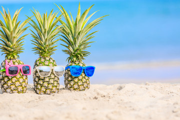 Attractive pineapples on the beach against turquoise sea. Wearing stylish mirrored sunglasses. Tropical summer vacation concept. Sunny day on the beach of tropical island.