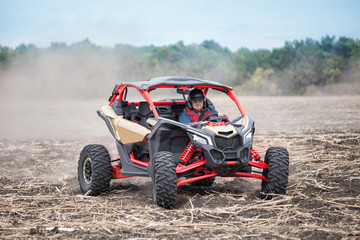 Smiling man at the wheel of quad bike standing in the field