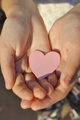 Pink paper heart on the girl's hands