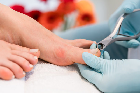 Close-up of the hands of a pedicurist wearing sterile surgical gloves, while using a toe nail clipper while shaping the nails of a female customer in a beauty salon