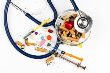 Cigarettes in a glass ashtray on a white background. Treatment of lung cancer. Stethoscope and medication.