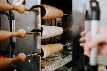 Cooking of trdelnik. Raw dough in oven. Bakery pastry food
