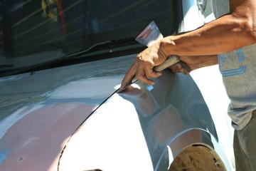 Automotive paint technician using paint on putty knife at bonnet , A part of the procedure to paint a new bonnet.