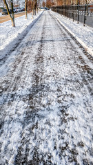 Close-up of asphalt in the snow. Road in the city in the winter, cleaned snow cleaned the street from the snow in the park.