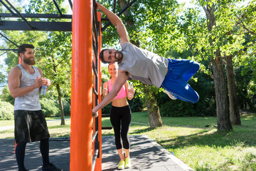 Strong and happy young man gripping a vertical bar while practicing human flag exercise with bent legs during street workout with his friends