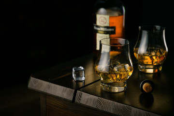 Whiskey in glasses with ice on rustic background