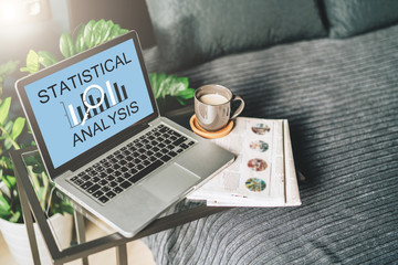 Bedroom,workplace without people,close-up of laptop with inscription statistical analysis on screen on table, desktop.Nearby is newspaper, cup of coffee, notebook. Nobody. Online marketing