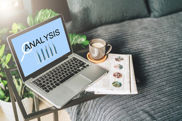 Bedroom,workplace without people,close-up of laptop with inscription analysis on screen on table, desktop.Nearby is newspaper, cup of coffee, notebook. Nobody. Online marketing