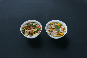 Two different Thai style spicy curry with pork and Thai Spicy Mixed Vegetable Soup with Prawns in two bowls on black background.