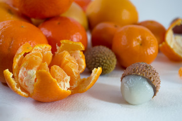 Mandarins on a white background with lobule, peel, citron and litchi. Side view, close. Citrus reticulata. Litchi chinensis.