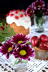 Three spring flowers. Easter cake and red coloured eggs in the background. Easter composition
