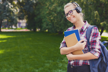 Student girl with books in park outdoors