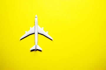 Miniature toy airplane on yellow background. Trip by airplane.