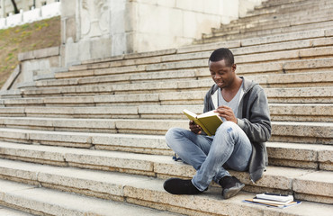 Smiling african-american student reading book on university stairs