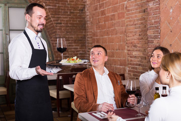 positive waiter placing order in front of guests