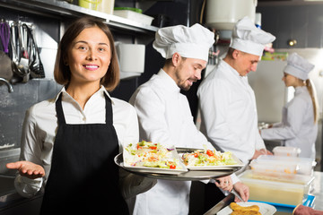 smiling woman waiter collecting dishes from restaurant's kitchen