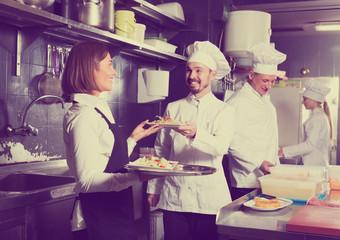 Adult female waiter taking ordered dishes