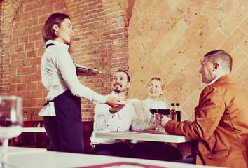Female waiter bringing order to visitors
