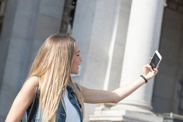 Pretty teenager taking a selfie with her mobile phone outdoor in the city