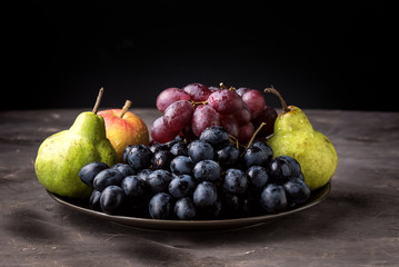 Beautiful Ripe Fruits on Plate Apple Pears and Grapes Dark Photo Dark Background Autumn Seasonal Fruits