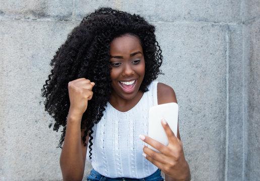 Africa american woman receiving good news on phone