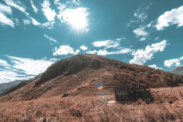 Wide-angle shooting of abandoned wooden shack or shepherd's house surrounded by mountains and hills of Altai, native grasses of pastures, teal sky, the sun at its zenith, Kuyus district, Russia