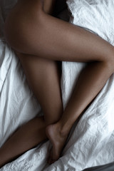 Sexy slender female legs on white bed