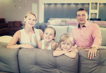 Man and woman with their children are choosing new sofa