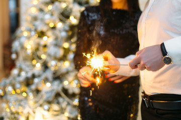 Gorgeous couple holds bengal fires standing before a shiny Christmas tree