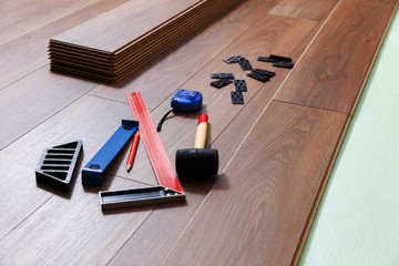 Laying a laminate flooring. On the floor are different carpenter's tools.