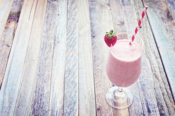 Delicious strawberry smoothie on wooden background