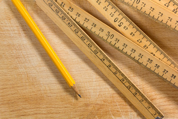 Measuring Stick and Pencil on a Wooden Table
