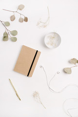 Home office desk with craft diary, pen, headphones and eucalyptus branches on white background. Flat lay, top view.