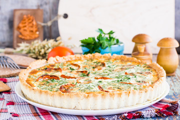 Homemade french quiche pie with tomato, cheese and herb on a plate