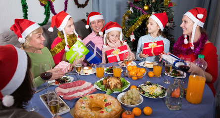 Happy family is sitting with gifts celebrating New Year