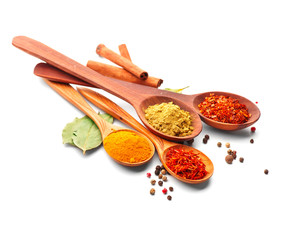 Spice. Various spices in wooden spoons over white background. Curry, saffron, turmeric, cinnamon