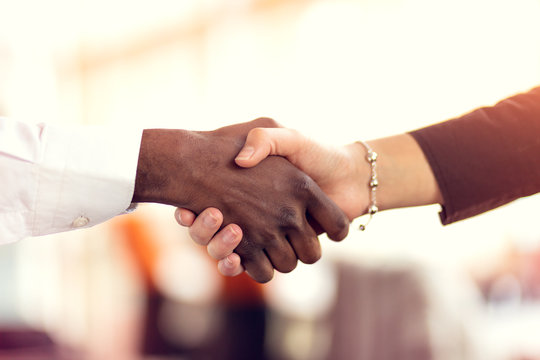 Closeup of White and Black shaking hands over a deal