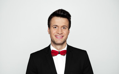 Have a good day! Close up portrait of smiling stylish handsome man in black suit and red bow tie isolated.