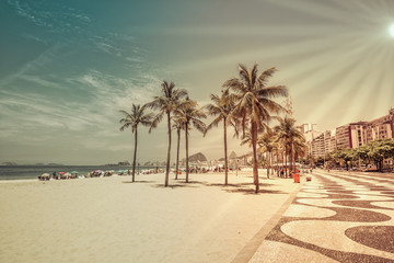 Copacabana Beach with palm trees, Rio de Janeiro, Brazil. Vintage colors with sun rays