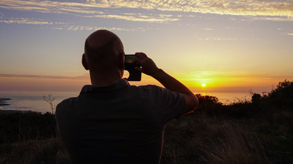 Young man takes a photo to the sunset with a smartphone with the sea in background