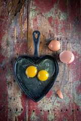 Valentines breakfast in heart shaped cast iron pan of two raw eggs and yolks