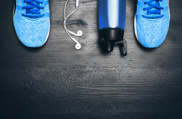 Flat lay shot of Sport equipment. Sneakers, water, earphones and phone on wooden background. Focus is only on the sneakers.